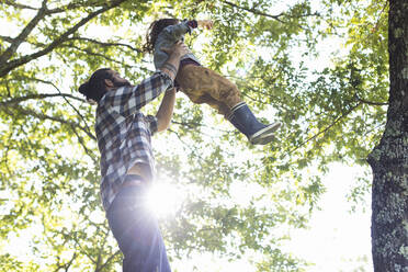 Father lifting up kid in the forest - SODF00103