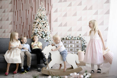Five children playing and eating cookies in the living room at Christmas time - EYAF00576