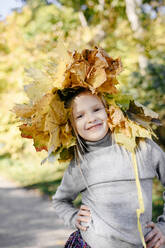 Portrait of smiling little girl with autumn wreath on her head - EYAF00590