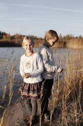 Siblings standing at riverside in autumn - EYAF00602