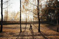 Little girl riding bicycle in autumnal park - EYAF00608