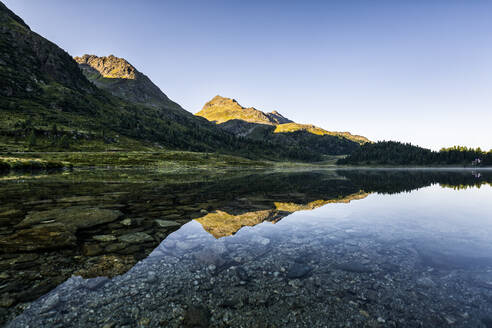 Austria, East Tyrol, Shiny lake reflecting mountains in Defereggen Valley - STSF02274