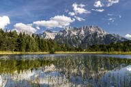 Austria, Tyrol, Scenic view of Weisssee lake reflecting Wetterstein Mountains and surrounding forest - STSF02289