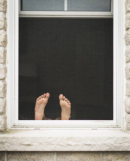 Open window with a child's feet on the ledge against the screen. - CAVF65176
