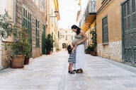 Alcúdia, Mallorca, Spain. Two year old girl hugging her pregnant mother on the street - GEMF03208