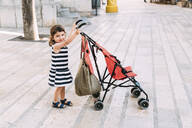Alcúdia, Mallorca, Spain. Two year old girl walking with her stroller in the street - GEMF03211