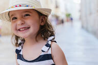 Alcúdia, Mallorca, Spain. Cute two year old little girl with straw hat smiling on the street - GEMF03214