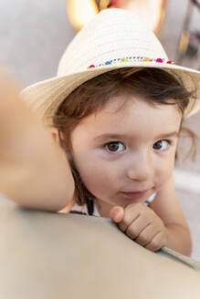 Portrait of little girl with brown hair and eyes wearing straw hat - GEMF03220