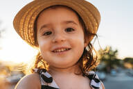 Portrait of smiling little girl wearing straw hat at sunset - GEMF03226