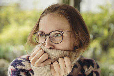 Young woman with glasses wearing fluffy sweater looking sideways - MFF04881