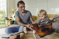 Portrait of toddler testingviolin while his father watching - MFF04890
