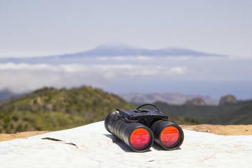 Im Vordergrund ein Fernglas auf einer Landkarte, im Hintergrund Teneriffa und der Teide vom Gipfel des Garajonay, wandern, Orientierung, Landkarte, Suchen, Nationalpark Garajonay, Unesco Weltnaturerbe, La Gomera, Kanarische Inseln, Kanaren, Spanien - MAMF00893