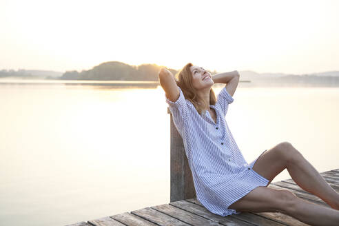 Happy mature woman sitting on jetty at a lake at sunrise - PNEF02178