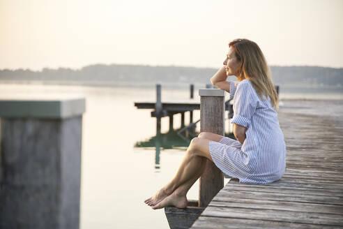 Mature woman sitting on jetty at a lake at sunrise - PNEF02181