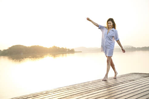 Mature woman balancing on jetty at a lake at sunrise - PNEF02184