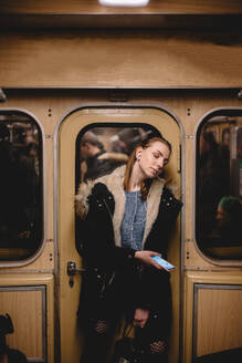 Young woman listening music on smart phone traveling  in subway train - CAVF65489