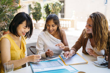 Female multicultural students meeting in a cafe organizing their class schedule - MPPF00096