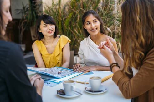 Female multicultural students meeting in a cafe organizing their class schedule - MPPF00111