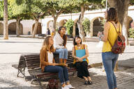 Female friends meeting in a city park - MPPF00114