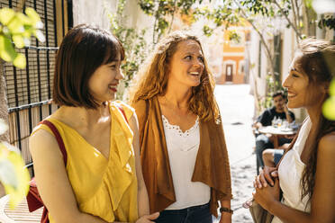Three happy female friends in a picturesque alley in the city - MPPF00117
