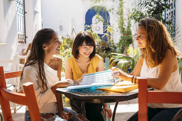 Female multicultural students meeting in a cafe organizing their class schedule - MPPF00123