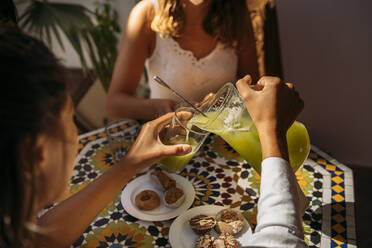 Woman serving lemonade to her friend in a Moroccan cafe - MPPF00126