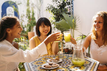 Three happy female friends meeting in a cafe clinking lemonade glasses - MPPF00129