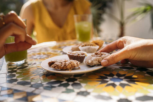 Close-up of woman taking a cookie from plate in a Moroccan cafe - MPPF00132