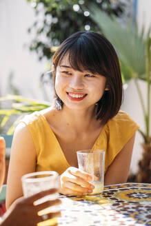 Portrait of smiling young woman with a friend at a cafe - MPPF00135