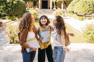 Three happy female friends with windblown hair visiting a formal garden - MPPF00147