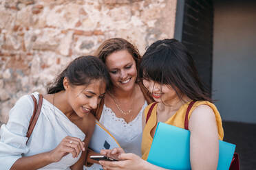 Three happy female friends looking at smartphone together - MPPF00150
