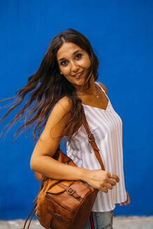 Portrait of beautiful young woman with backpack at a blue wall - MPPF00180
