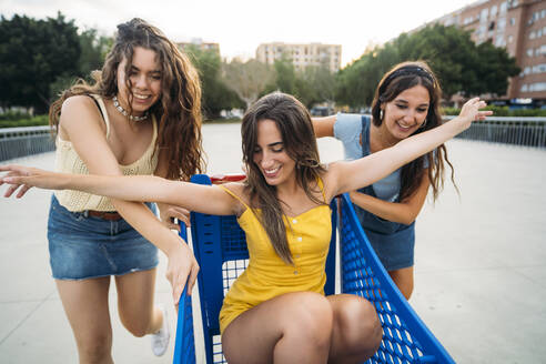 Three playful female friends with shopping cart in the city - MPPF00192