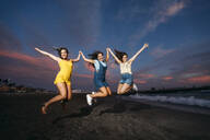 Three carefree female friends jumping on the beach at sunset - MPPF00201