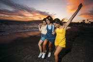 Three happy female friends on the beach at sunset - MPPF00204