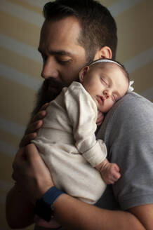 Newborn baby girl sleeping on father's shoulder at home in soft light - CAVF65565