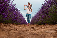 Happy mother and daughter walking among lavender fields in the summer - CAVF65574