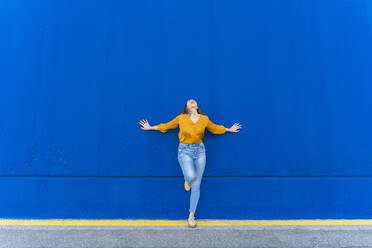 Young screaming woman leaning on blue wall - AFVF04064