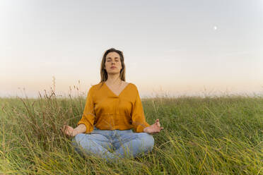 Young woman sitting on a meadow and meditating in the evening - AFVF04067