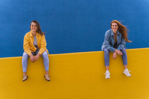 Young smiling women sitting on an orange wall - AFVF04073