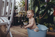 Baby boy sitting in baby bath on the balcony, try in to get up - MFF04897