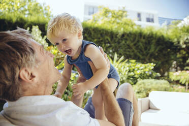 Father sitting in garden, playing with his little son - MFF04915