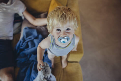 Little boy with pacifier standing on couch, looking up at camera - MFF04924