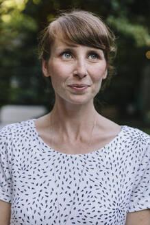 Woman standing in garden, smiling - MFF04933