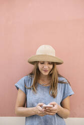 Woman standing at a pink wall using smartphone - AHSF00934