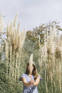 Woman holding reed, Aveiro, Portugal - AHSF00940