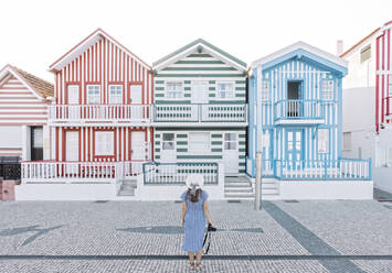 Rear view of woman with camera in front of striped houses, Costa Nova, Portugal - AHSF00946
