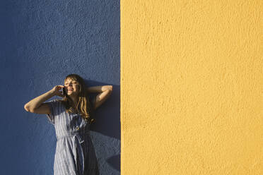 Happy woman on the phone in front of yellow and blue walls - AHSF00949