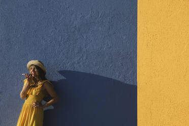 Woman in a yellow dress using smartphone in front of yellow and blue walls - AHSF00961