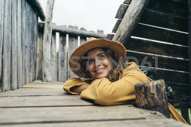 Young smiling woman wearing yellow coat and hat on top of wood stairs, looking sideways - MTBF00003 - Mikel Taboada/Westend61